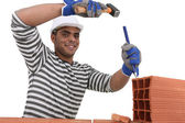 Man chipping away at brick — Stock Photo