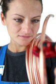 Female plumber at work with copper piping — Stock Photo