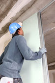 Worker slotting plasterboard into place — Stock Photo