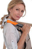 Female carpenter with hammer and wooden frame — Stock Photo