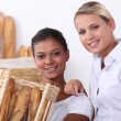Two shop assistants working in a bakery - Stock Photo