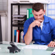 Stock Photo: Manual worker at an office desk