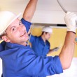Electricians working on roof - Stock Photo