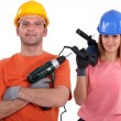 Female and male tradespeople holding electric drill — Stock Photo