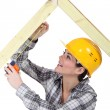 Stock Photo: Female carpenter measuring wooden frame