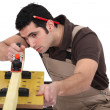 Stock Photo: Carpenter planing plank of wood