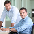 Disabled worker with colleague — Stock Photo
