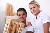 Two shop assistants working in a bakery — Stock Photo