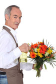 Florist spraying flowers — Stock Photo
