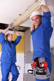 Electricians installing neon on ceiling — Stock Photo