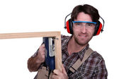 Man with an electric jigsaw — Stock Photo