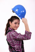 Woman raising her hard hat — Stock Photo