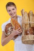 Bageri arbetstagaren innehar korg med bröd — Stockfoto