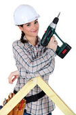 Female construction worker holding a battery-powered screwdriver — Stock Photo
