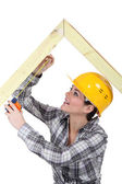 Female carpenter measuring wooden frame — Stock Photo