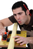 Carpenter planning timber — Stock Photo