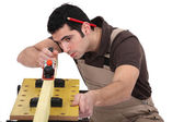 Carpenter planing plank of wood — Stock Photo