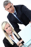 Boss looking at a laptop with an employee — Stock Photo