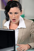 Shocked woman reading an e-mail — Stock Photo