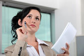 Reflective brunette holding notepad and pen — Stock Photo
