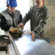 Apprentice being shown how to cut sheet metal — Stock Photo