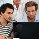 Men sitting around a laptop — Stock Photo #10021001