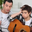 Stock Photo: Man teaching to boy how to play guitar