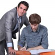 Foto Stock: Teacher helping male teenager