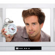Man holding alarm clock trapped in the television — Stock Photo #10024468
