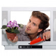 Stock Photo: Man holing flowerpot and a trowel looking through a television frame