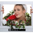 Woman in festive outfit escaping from television - Stockfoto