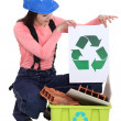 Pretty female bricklayer holding recycling logo — Stock Photo
