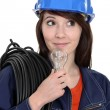 Stock Photo: Female electrician with a lightbulb