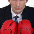 Young businessman with boxing gloves — Stock Photo