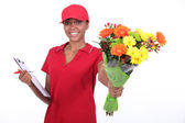 A delivery woman bringing a flowers bouquet — Stock Photo