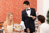 Waiter serving plate of food — Stock Photo