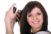 Mulher aplicando spray de cabelo — Foto Stock
