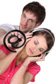 Woman listening to music and a man with an at symbol — Stock Photo