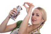 A blonde woman collecting batteries for recycling — Stock Photo