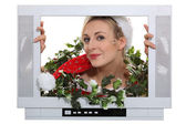 Woman in festive outfit escaping from television — Stock Photo