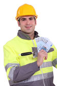 Manual worker holding weekly salary — Stock Photo