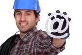 Electrician holding an @ sign — Stok fotoğraf