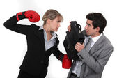 Businessman with boxing gloves hitting man — Stock Photo
