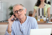 Elderly woman chatting on the phone whilst young helper works in the kitchen — Stock Photo