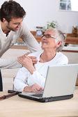 Man explaining to senior woman how to use computer — Stock Photo