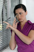 Paranoid woman looking through the window blinds — Stock Photo