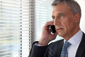 Executive phone in front of window — Stock Photo