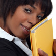 Stock Photo: Businesswoman holding folder against face