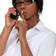 Black bespectacled woman on the phone with finger before her mouth — Stock Photo #10082970