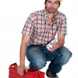 Builder carrying plans and a toolbox — Stock Photo